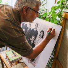 Issa Saharkhiz, ein prominenter iranischer Journalist, signiert ein Foto der sieben ehemaligen Vertreter der Bahá'í im Iran.